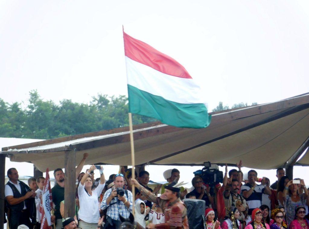 Vermes István meglobogtatja a magyar zászló a küldöttek előtt (Fotó: Pósa Dénes)